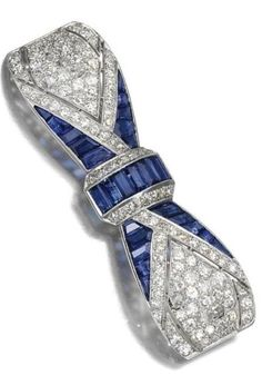 AN ART DECO SAPPHIRE AND DIAMOND BROOCH, 1920s. Designed as a bow, pierced and millegrain-set with calibré-cut sapphires and circular-cut diamonds. #ArtDeco #brooch