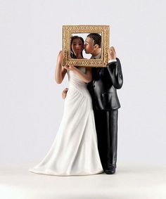"""Picture Perfect Hispanic Couple Wedding Cake Topper made of hand painted porcelain. The bride is wearing an elegant white dress with an asymmetrical design. The groom is wearing a handsome black suit, kissing his bride. The couple is holding a gold picture frame, showing that they are """"picture perfect"""" for each other."""
