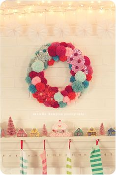 Mixing a pompom wreath with a vintage holiday village and candy-striped stockings gives this mantle festive flair.