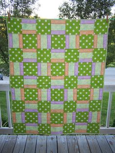 Modern Crib Quilt for baby with a soft flannel back, in bright green with white polka dots, lavender, peach and light green prints.