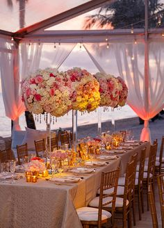 The wedding tent was overflowing with lush pink and white blooms, beachy gold accents, and an elegant grouping of crystal chandeliers overhead. You don't want to miss any detail of this Bahamas beach wedding.