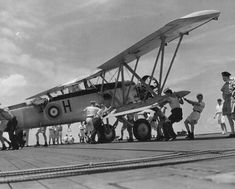 An ex-Royal Canadian Air Force Blackburn Shark biplane torpedo bomber is manhandled by crews from HMS Thane as they learn the new trade of moving heavy aircraft on deck while at sea. The aircraft was deemed obsolete by the RCAF and the crew was told to ditch the Shark when no longer needed.