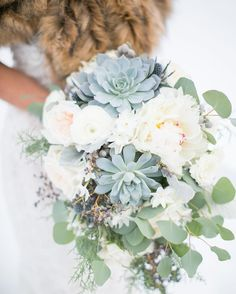 Blue, white and green winter bridal bouquet featuring succulents, peonies, ranunculus and privet. Plum Sage Flowers