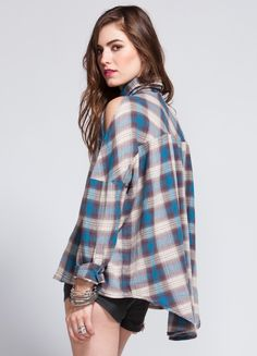 """Unif's Bare Shouldres button up channels Paul Bunyon with a Wasteland twist. Features basic front button down detailing, longer back hem, and cut out sections in the sleeves for a feminine spin on an otherwise basic menswear design.    100% polyester  25"""" length  Model is wearing size S"""
