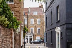 Restored Grade II listed townhouse in Chelsea, London. Yellow brick townhouse viewed through the laneways.