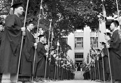 Young men dressed in caps and gowns stand in two lines leading up to the steps of a building, each holding a flag, at the University of Michigan commencement at Ferry Field in Ann Arbor June 17, 1937. (Detroit News Archives)
