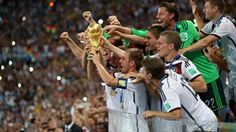 Philipp Lahm of Germany lifts the World Cup trophy to celebrate with his teammates