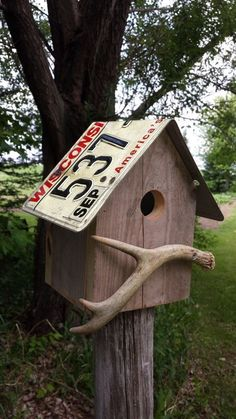 Rustic looking wren birdhouse with Wisconsin or Minnesota license plate roof and whitetail deer antler perch. The hole is 1 so only wrens, chickadees and nuthatches will fit. NO SPARROWS! The roof is screwed on for easy removal for end of the s Homemade Bird Houses, Bird Houses Diy, Bird House Plans, Bird House Kits, Bird House Feeder, Bird Feeders, Birdhouse Designs, Bird Boxes, Toy Boxes