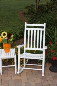 Two Rocking Chairs With A Small Drink Table Between Them.