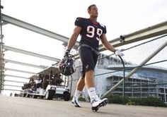 Texans defensive end J.J. Watt walks across a bridge on his way to the first practice of training camp at The Methodist Training Center on Friday.