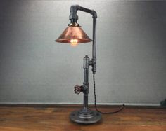 This industrial table lamp uses a 60 Watt Edison Bulb which hangs from a vintage style cloth cord and offers subtle but brilliant ambient light. The 8 copper shade will stand out in any room...  We have had customers use this lamp as an accent in many styles of decor from the rustic to the industrial.  The table lamp is constructed from industrial style black iron piping. The height of the shade can be adjusted by threading the cord the metal loops.  Dimensions:  Height - 26in Width - 8in…