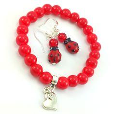Komplet biżuteriidamskiej wykonany ręcznie. Kolczyki i bransoletkaz czerwonych koralików szklanych i elementów w kolorze srebrnym. Dodatkowo zawieszka charms w kształcie serca. Kolczyki biedronki lampwork.