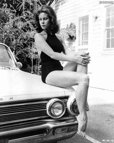 Elizabeth Montgomery sitting on a Buick.