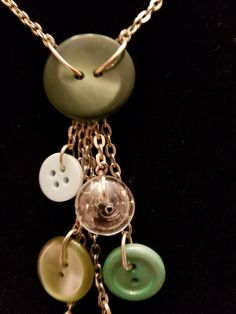 Cascading antique button necklace with greens, whites, and a glass button.