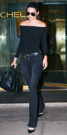Kendall Jenner wears an off-the-shoulder black top, belted flare jeans, a black satchel, pumps, and aviator sunglasses