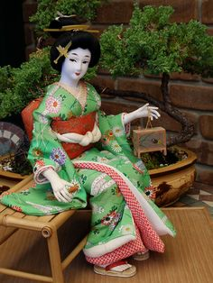 """""""This is a seated Geisha doll from the 1970s, holding an insect cage with a firefly inside. She is either meant to represent a woman of the Genroku period (1688-1703), when catching fireflies was a common pastime in the summer months, or a Geisha dressed in the Genroku-style at the end of the Meiji period (early 1900s)."""""""
