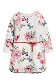 Een jurk van dunne joggingstof met een geprint dessin. De jurk heeft een afneembaar riempje van gevlochten imitatiesuède en lange raglanmouwen met een vastg