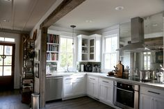 More substantial shelves/cabinets either side of sink ... not sure that I like the heavy wood beam at kitchen entrance