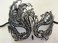 Black metal mardi gras mask with rhinestone accents and black ribbon ties.