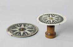 J.M. Kleman & Zoon | Kompaspen, J.M. Kleman & Zoon, George Stebbing, 1825 | Kompaspen met robijnen punt op een houten voetstuk, met roos. De roos heeft een messing dop in het midden met gat voor de pen onderin: het draaien van de roos werd door de gebruikte materialen verbeterd, terwijl het schommelen door de vermeerdering van het wrijvingsoppervlak van de robijn werd verminderd. De roos, die zwaar beschadigd is, kan gedraaid worden binnen een buitenrand, waarop een schaal in graden per…