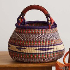 "Violet/Red 5-color basket | Perfect for storage, carriage, or colorful decor, these Bolga baskets make an extraordinary impact. In one of the most impoverished areas of Ghana, women weavers are earning a sustainable income as they craft these distinctive elephant grass baskets. Leather-wrapped handle is 18""l. serrv.org"