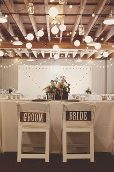 OUr chairs will be different, but the signs are still a necessity; mason jars hung from the ceiling for extra sparkle?! nice!