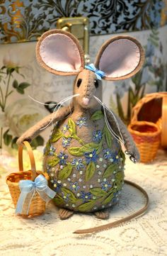 This sweet seamstress mouse is a hand stitched pincushion made from tan wool blend felt, trimmed in vines with blue embroidered flowers and glass beads. She has a blue ribbon next to her ear as well as on her basket. Her large ears are lined with pink cotton and the tail is made of faux suede. The seamstress mouse is carrying her trusty mini scissors and has a mini basket to hold your thimble or any sewing treasure of your choosing. Ive also added a few special jeweled pins to get you…