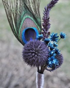 Look at this gorgeous and unique Peacock Feather Boutonniere (photo from Madison House Designs). Create this yourself using Peacock Eye Feathers, Dried Echinops, Dried Lavender, and dyed starflowers. Wrap the stems in floral tape and then the ribbon of your choice and you will have a stunning boutonniere for your wedding or other special occasion.  All of these items are available now in our store- shop now!⁣⁣ #peacockfeathers #boutonniere #weddinginspiration #echinops