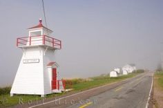 Port George lighthouse next to the road in Port George, Nova Scotia in Canada as the fog starts to lift.