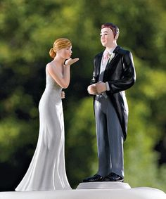 Blowing Kisses Wedding Cake Topper made of hand painted porcelain.  The bride is wearing a traditional, elegant white wedding dress. She is posed blowing a kiss to her groom. The groom is wearing a traditional morning suit complete with a long black jacket, pink tie, and gray-blue pants.