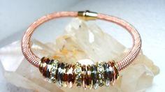 Pulseira Malha Italiana Rosê com Pingentes.    Os pingentes são anéis dourados, prateados, rosê e strasses.    Fecho imantado dourado.    Largura da pulseira: 18,5 cm R$ 65,00