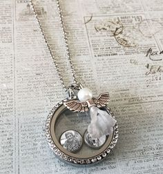 "This kit makes a complete photo locket with 6 floating photo charms. Includes standard size floating photo locket pendant with dangling angel charm. Includes matching 20"" necklace chain with extender"
