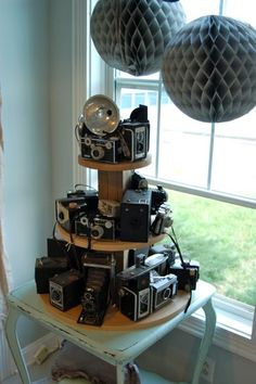 Cool way to display vintage cameras...if possible, make the stand a turnable one for quick access to all the cameras