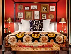 Tangerine Lacquer Walls, Black Four Post Bed, Tribal Textiles, and Eclectic Art Collection, all used to Create a Very Handsome & Masculine Bedroom.