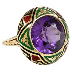 An Art Deco gold and purple synthetic sapphire ring set in a red, green and black enameled surround, in 14k. Circa 1925s