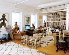 Room/Style: Family Room, Contemporary     Notes: In the living area, the Karl Springer cocktail table and Milo Baughman stools are circa 1970; the vintage Moroccan carpet in the foreground is from Madeline Weinrib Atelier, and the oilon-paper work above the Samsung television is by Weinrib.