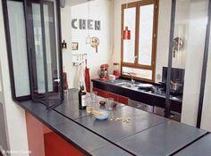 Ici, le bar du salon devient plan de travail côté cuisine. Des vitres créent une séparation avec cette petite cuisine rouge tout équipée !