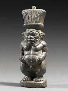 Statuette représentant le dieu Bès. Il est nu, debout, grimaçant, les mains posées sur les cuisses. Le visage présente une barbe aux mèches bouclées, et est coiffé des hautes plumes finement gravées. Un reste de tenon en bronze, fiché au sommet de la coiffe, indique l'utilisation probable en manche de miroir. Stéatite et bronze (tenon). Très belle conservation. Egypte, Epoque Ptolémaïque. H_11,5 cm. -Pierre Bergé & associés-