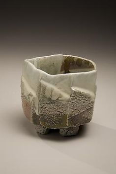 Masterworks by Nishihata Tadashi  Tamba ware glazed footed teabowl with faceted carved exterior, 2007  Wood-fired stoneware with creamy ladle-poured ash and iron-oxide glazes  3 7/8 x 5 1/2 x 5 inches