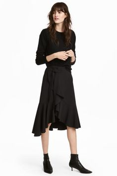 Een midirok van elastische, geweven kwaliteit met een vastgestikte overslag en brede volants voor. De rok heeft strikbanden aan de zijkant, een naad met een