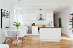 cuisine blanche avec plan de travail en bois, chaises eames, table tulipe, parquet bois et des touches métal noir.