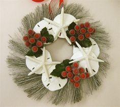 """Small Seashell Christmas Wreath 11""""diameterA natural twig wreath sprayed white with real Sand Dollars and Starfish and a few sprigs of faux berries and leaves.I added a pretty grosgrain ribbon from which to hang.Measures approximately 11"""" Diameter, ribbon adds another 2"""" Made from real sand dollars and starfish Delicate construction. $39.00"""