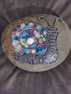 Mosaic snail with ball chain on a rock.