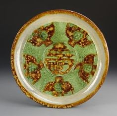 China, Liao Dynasty, Sancai plate in a speckled green and brown glaze, underside unglazed, with bird figure motifs around the center, containing an auspicious symbol. Diameter 10 in.