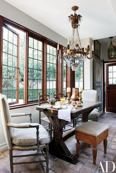 An assortment of Provençal chairs mingle with an English trestle table and an Italian stool and chandelier in the breakfast area.