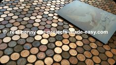 Real random pennies covering a floor, grouted with black sanded grout.