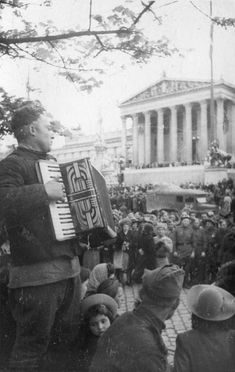 A Soviet soldier plays the accordion at the parliament building in Vienna. Location: Vienna, Austria. Time taken: May 1945. Author: Anatoly Morozov