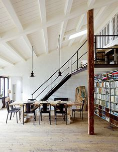 Rustic reclaimed beams and floor with industrial metal stairs and loft area.