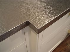Stainless steel countertops come in a range of finishes, including brushed, polished, quilted and hammered (shown). Textured styles can add dimension and mask fingerprints. Photo courtesy of Brooks Custom