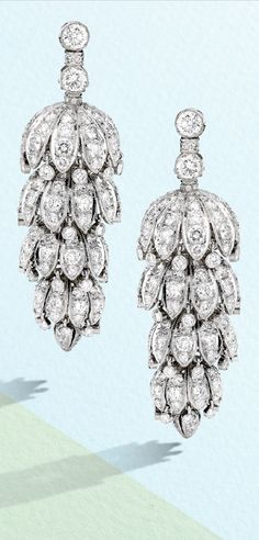 A Pair of Art Deco Diamond Earclips, 1930s. Designed as lanterns with articulated segments, set with numerous round diamonds.